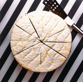 Round cake with white cream and glaze cut in pieces for serving placed on black and white striped surface
