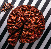 Sweet chocolate pie with chocolate bar on striped black and white surface