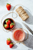 Fresh homemade strawberry juice in glass jar wrapped with twine placed on marble surface