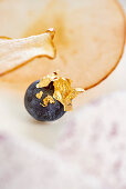 A blueberry with gold leaf as a cake decoration