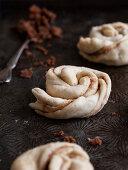 Dough shaped into cinnamon buns, ready to bake