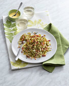 Spinach tagliatelle with a cheese sauce, ham and roasted nuts