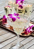 Glasses of prosecco lined up on a copper tray outside, with purple orchids