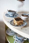 Tiramisu slice on a blue plate on marble with coffee and chocolate powder falling