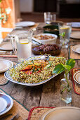 Tray of homemade sprout salad on a wooden table with plates and props and jugs of drinks