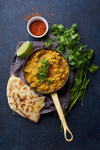 Vegan Indian red lentil curry soup dal with rice naan