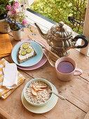 Breakfast with tea, porridge and bread by an open window