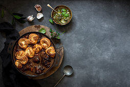 Braised oxtail with scroll scone dumplings and herbed green salsa