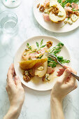 Female hands holding a plate of pear salad with walnuts, prosciutto, arugula and blue cheese. Dinner appetizer on marble table
