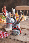 Tins of cutlery on a rustic wooden table