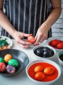 Ein gefärbtes Ei schälen