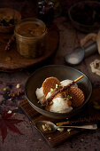 Vanilla ice cream topped with caramel sauce, mini stroopwafel cookies, chopped nuts and a chocolate stick