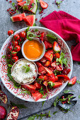 Tomato salad with strawberries and melon, with pepper and feta dips