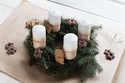 Handmade Advent wreath with fir branches, biscuits and white candles