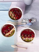 Smoothie bowls with cherries, cereals and pistachio nuts