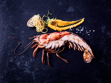 A cooked lobster on a dark surface