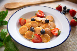 Minipancakes cereal in a bowl with milk and fruit