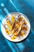 Fried fish fillets on an orange and onion salad with fennel and edible flower petals