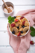 Vegan mini pancake bowl with berries, sugar syrup and chocolate