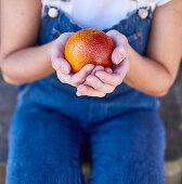 Girl holding a blood orange