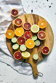 Various halved citrus fruits on wooden board