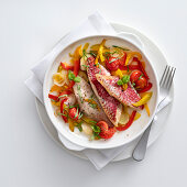 Oven-roasted red mullet fillets with a pepper medley and cherry tomatoes