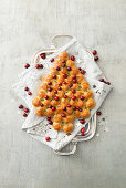 Christmas tree-shaped yeast bread decorated with thyme and cranberries
