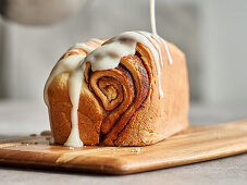 Glazing a cinnamon roll cake with icing
