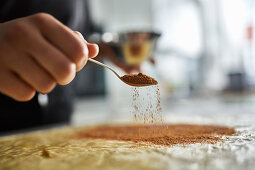 Preparing cinnamon roll cake: sprinkling dough with cinnamon
