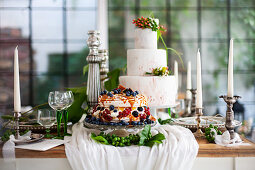 Two celebration cakes, candlesticks and wine glasses on festively set table