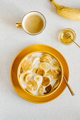 Pancake cereal in a bowl of milk with banana and honey