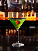 A green cocktail with a raspberry in a bar