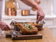 Grilled crispy roast pork being carved
