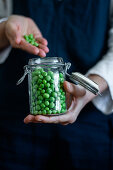 Person in apron standing with glass can of fresh green peas