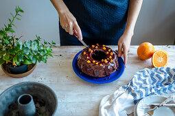 Cutting chocolate bundt cake with coconut sugar and orange chocolate glaze