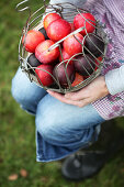 Woman holding a basket with plums