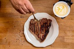 Seasoning a grilled porterhouse steak