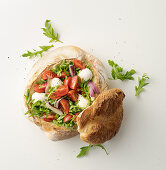 Tomato and mozzarella salad with rocket served in a loaf of bread