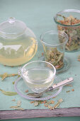 Linden blossom tea in a tea filter and brewed in a glass jug and cup
