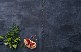 Dill, mint and pomegranate on a dark surface