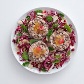 Boiled veal and beef on a bed of lettuce with pomegranate seeds