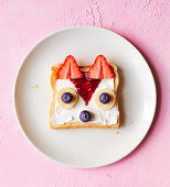 A fruit fox made from a slice of toast spread with cream cheese