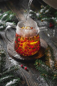 Brewing black tea with viburnum berries and lemon with fir branches and snow