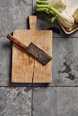 A meat cleaver on a chopping board next to fennel bulbs