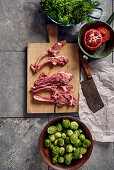 Lamb chops on a wooden surface next to Brussels sprouts