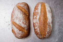 Two freshly baked loaves of brown bread