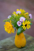 Small bouquet of marigolds, fennel blossoms and daisies in an ornamental pumpkin as a vase