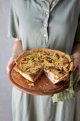 Woman holding cheese tart with walnuts