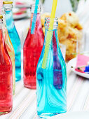 Colorful glass bottles with sparkling water and drinking straws
