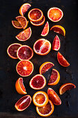 Blood oranges in slices and wedges on a black background